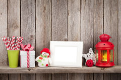 Christmas candle lantern, photo frame and decor. In front of wooden wall with copy space Stock Image