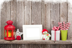 Christmas candle lantern, photo frame and decor. In front of wooden wall with copy space Royalty Free Stock Photos