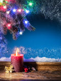Christmas candle light and frozen window. Christmas background Stock Photos