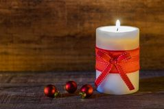Christmas candle light with red bow and balls. Stock Photos