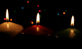 Christmas Candle Line. Three Christmas candles up close, with festive lights in the background Royalty Free Stock Photo