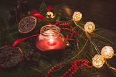Christmas candle. Magic christmas mood with burning candle and glittering christmas tree lights stock photo