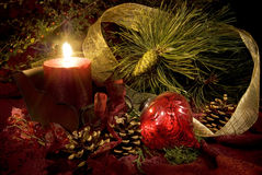 Christmas Candle and Ornament. Low key still life of Christmas decorations in reds and greens Stock Photos