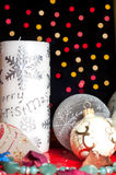 Christmas candle over lights background. Christmas candle, globes, balls, tinsel and flowers with lights background Stock Photo