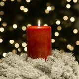 Christmas Candle Red. Red candle in front of a blurred Christmas tree Royalty Free Stock Photography