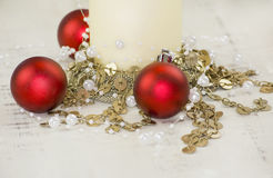 Christmas candle and red baubles. With gold chain and pearls Stock Image