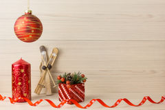 Christmas candle with ribbon and gift skiing red  balls on wooden background. Royalty Free Stock Image