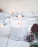 Christmas candle and rustic decoration on wood table with Christmas lights background in night party. Stock Photos
