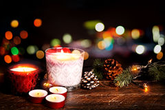 Christmas candle and rustic decoration on wood table with christmas lights background in night party Stock Image