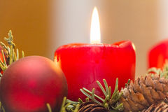 Christmas candle. Shining red xmas candle in an advent wreath Stock Photos