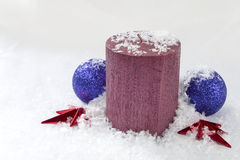 Christmas Candle Snow and Baubles. Christmas candle arranged with baubles covered in snowflakes against a white background with copy space Stock Images