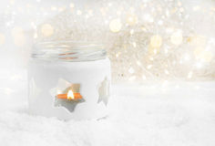 Christmas Candle in the Snow with Lights and Sparkle Stock Photos