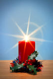 Christmas candle with starburst and holly. Royalty Free Stock Photo