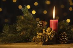 Christmas candle with statuette of baby Jesus. Christmas candle with a statuette of baby Jesus, pine cones, and fir branches. Shot with blurred lights stock photo