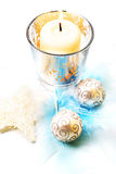 Christmas candle, still life. Christmas decoration: creamy candle and star, with silver baubles and feathers Stock Photos
