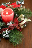 Christmas Candle Table Decoration. A lighted red Christmas candle table decoration amung green boughs, snow, and red ribbons. It is celebrating this joyous Royalty Free Stock Photography