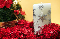 Christmas candle and tinsel. Christmas candle on a yellow background Stock Images