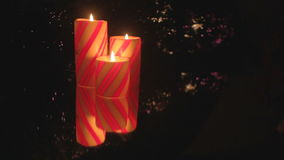 Christmas candle trio with reflections. Trio of red striped Christmas candles with reflections and shimmering lights stock footage