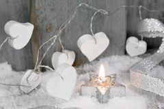 Christmas candle in white with hearts, wood and snow for decorat Stock Photos