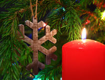 Christmas - candle and wooden snowflake on fir Stock Photography