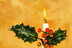 Christmas candlelight. Candle, holly & berries in front of hand painted gold background stock image