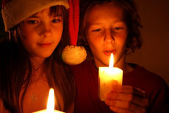Christmas candlelight. Brother and sister looking to Christmas candlelight Royalty Free Stock Photos