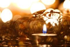 Christmas candlelight decoration. Burning candle against Christmas decoration and candlelight background Royalty Free Stock Photography
