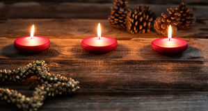 Christmas candlelight with glowing red candles and golden star symbol. Christmas candlelight background with glowing small red candles, fir cones and big golden royalty free stock images