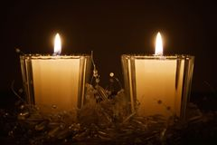 Christmas candles. Two white bright christmas candles in dark Stock Images