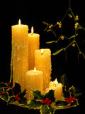 Christmas candles. A still life composition of Mistletoe, holly and church candles, denoting the symbols of christmas Stock Photos