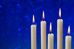 Christmas Candles. Burning candles on a blue defosussed background Stock Image
