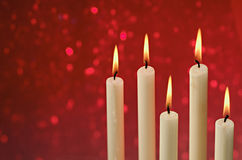 Christmas Candles. Burning candles on a red defosussed background Royalty Free Stock Image