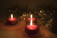 Christmas candles. Three lit little red candles and christmas ornament royalty free stock image