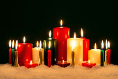 Christmas candles against black background. Stock Photos