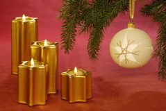 Christmas candles and bauble. Four golden candles and Christmas bauble on red background royalty free stock photography