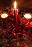 Christmas candles & baubles. Red christmas candles ,decorations of ribbon and baubles in a heart shaped candle holder Royalty Free Stock Photography