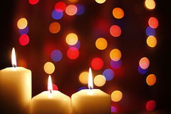 Christmas candles, with bokeh spot lights. In the background royalty free stock image