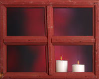 Christmas candles burning. Christmas candles burn as seen through an old window Royalty Free Stock Image