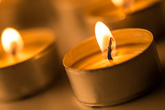 Christmas candles burning at night. Abstract candles background. Golden light of candle flame. Stock Photo