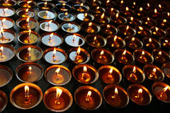 Christmas candles burning at night. Abstract candles background. Golden light of candle flame. Stock Image
