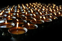 Christmas candles burning at night. Abstract candles background. Golden light of candle flame. Royalty Free Stock Image
