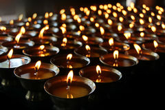 Christmas candles burning at night. Abstract candles background. Golden light of candle flame. Royalty Free Stock Images