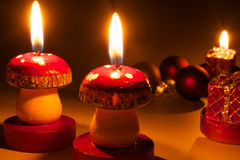 Christmas candles - Candles light. Mushroom candles and christmas balls on dark background Royalty Free Stock Photography