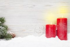 Christmas candles and fir tree. Branch covered by snow in front of wooden wall. Xmas backdrop with space for your greetings Royalty Free Stock Photos