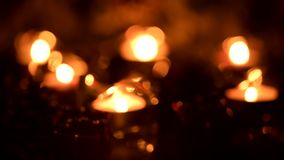 Holiday candles twinkle in an atmosphere of floating diffused lights. Christmas candles flickering in an atmosphere of floating diffused lights stock footage