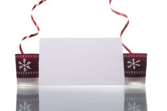 Christmas candles holding a blank card Royalty Free Stock Photos
