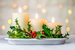 Christmas candles and holly berries with bokeh. Royalty Free Stock Images