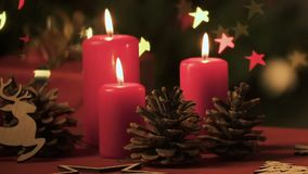 Christmas candles, pinecones and gift against background of fairy star lights. Stock footage stock video footage