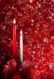 Christmas candles. A red and white candle with flame and red bows at the base.  Christmas concept Royalty Free Stock Photo