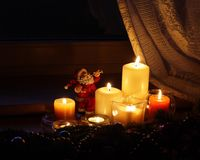 Christmas candles with Santa Claus. Candles  and Santa Claus with Christmas decorations in dark interior Royalty Free Stock Photo
